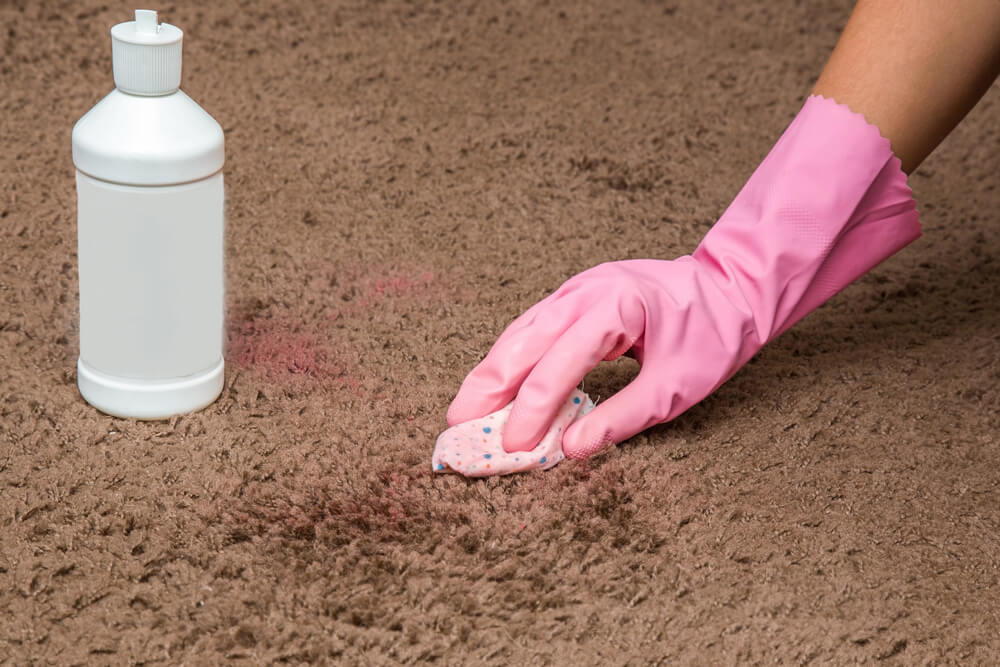 A person cleaning dried nail polish off their carpet.