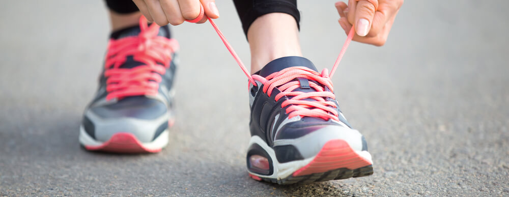 A person tying their running shoes.