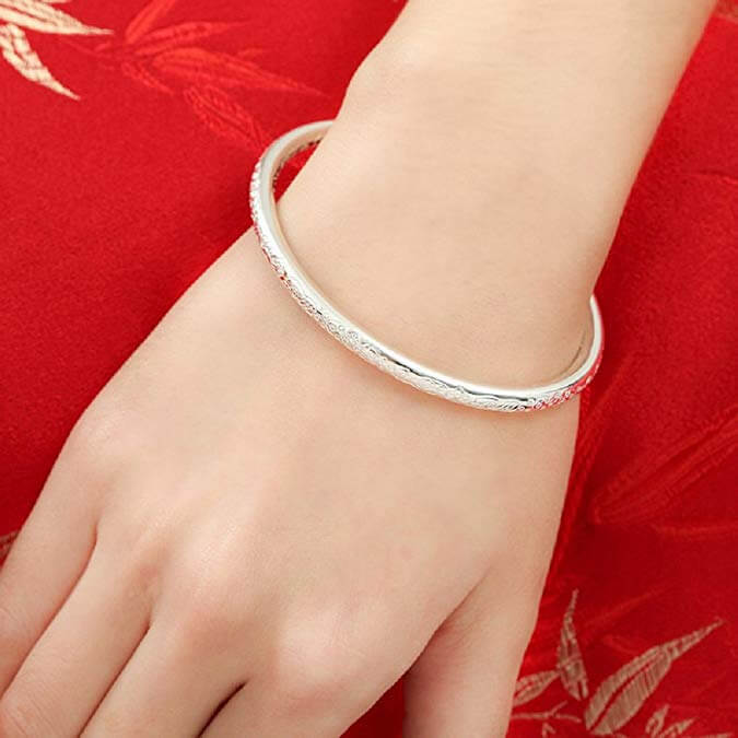 A closeup of the Merdia Sterling Silver Bangle on a woman's wrist.