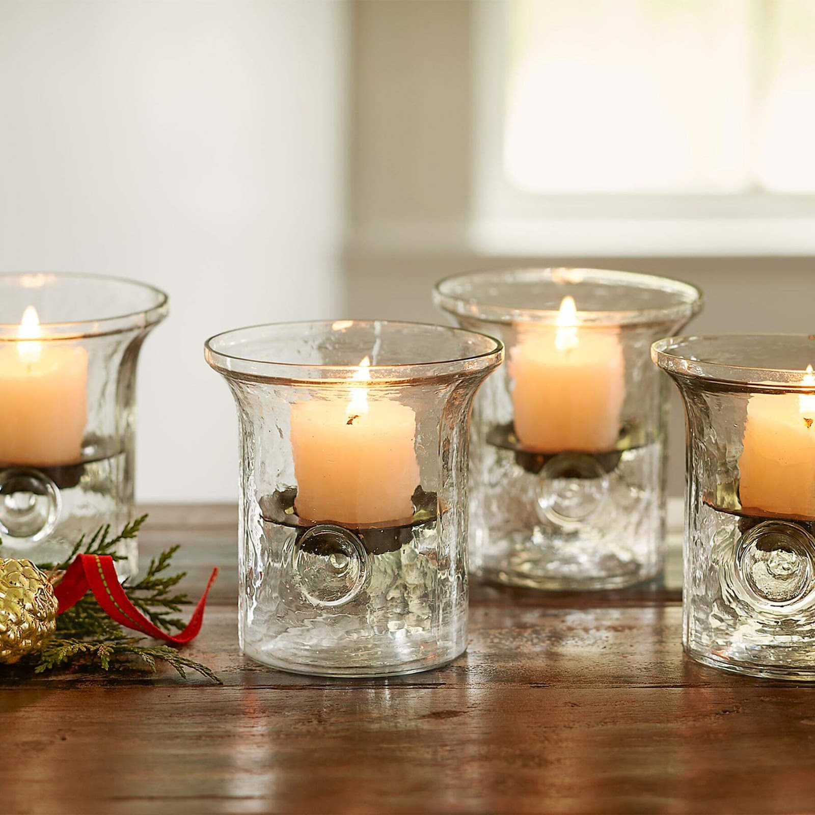 Four Blown Glass Hurricanes with lit candles.