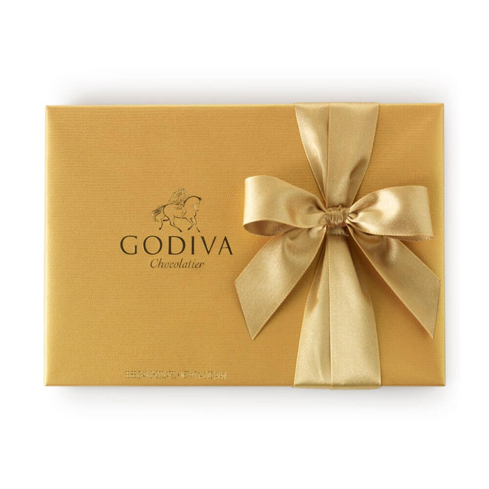 A gold box with a gold ribbon with Godiva chocolate inside.