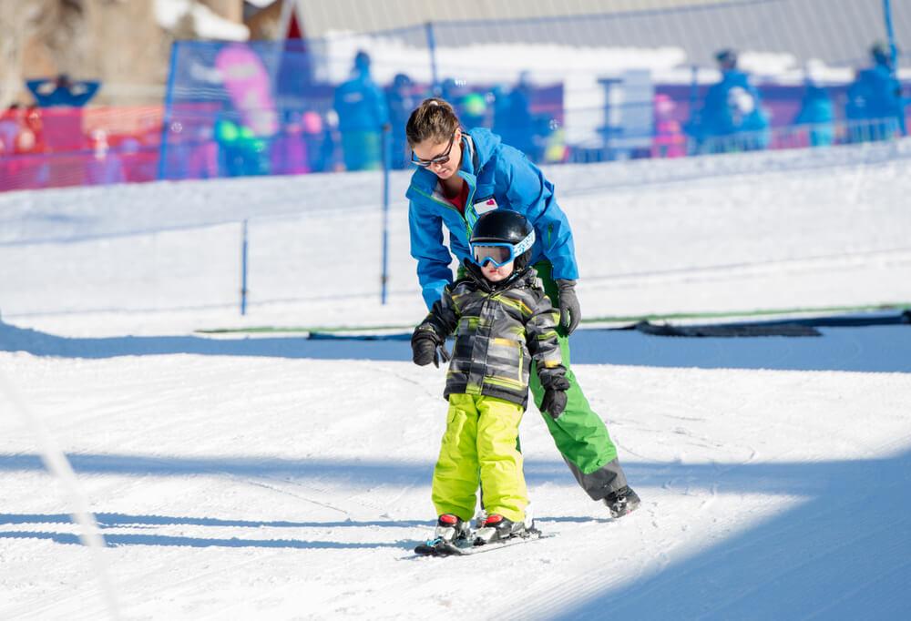 A young boy taking a ski lesson.
