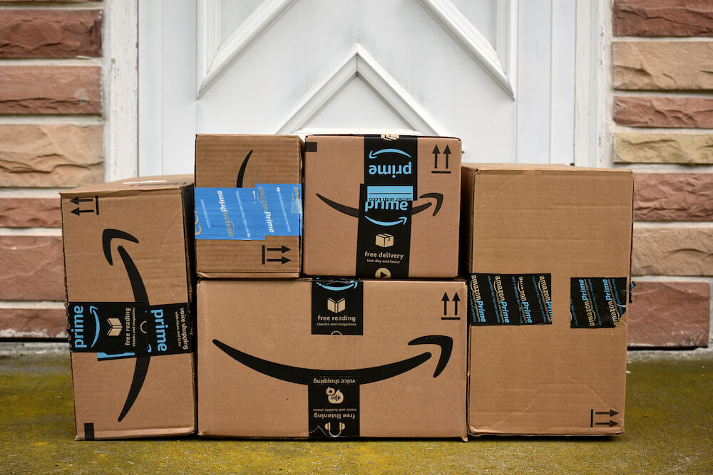 Amazon boxes piled on a doorstep.