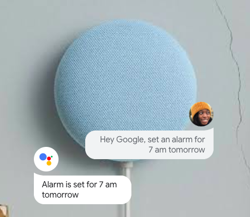 A Google Nest Mini with a dialogue box showing how you can ask it to set an alarm tomorrow.