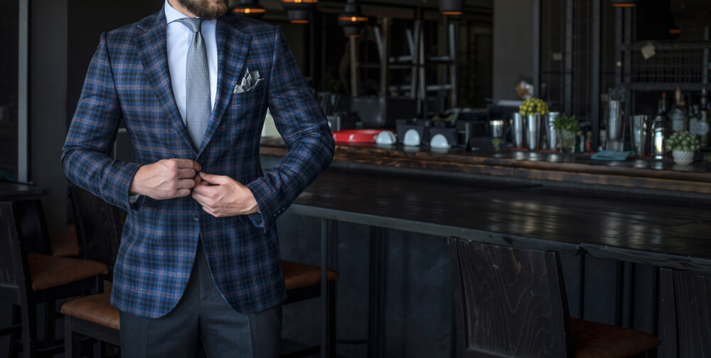 A man wearing a custom plaid suit in a nice bar.