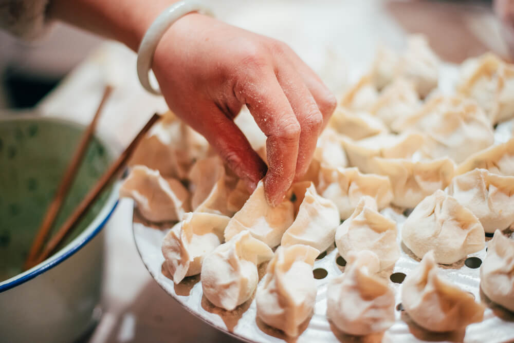 A person making Chinese dumplings.