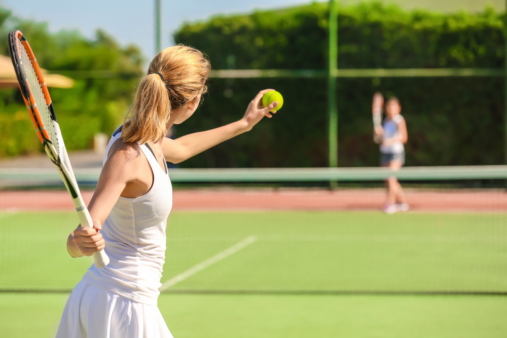 A woman serving a tennis ball.