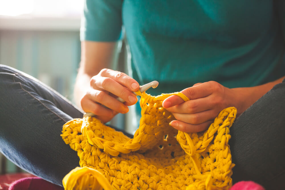 A person crocheting with yellow yarn.
