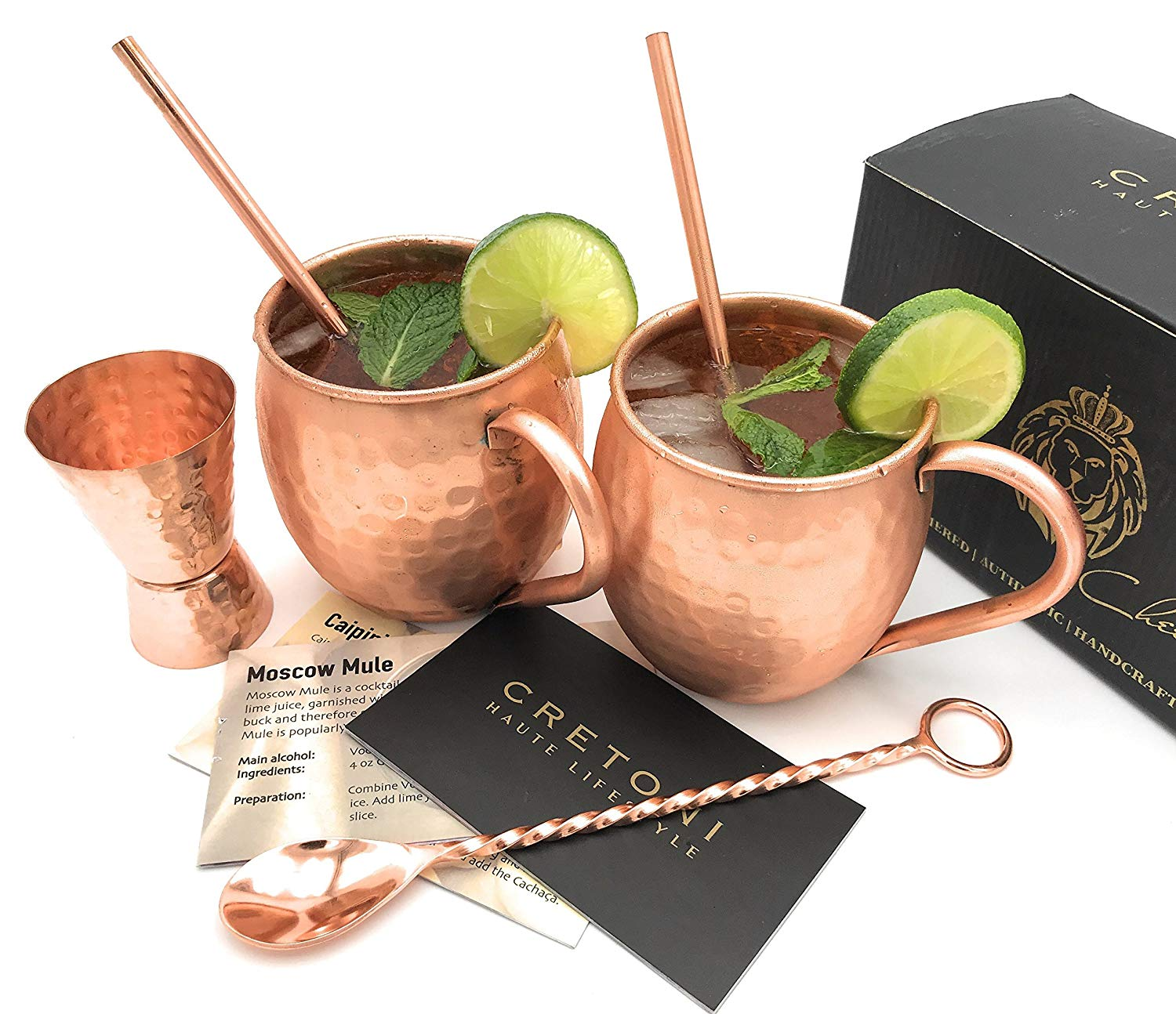 Moscow Mules in brass cups with brass straws and fresh limes.