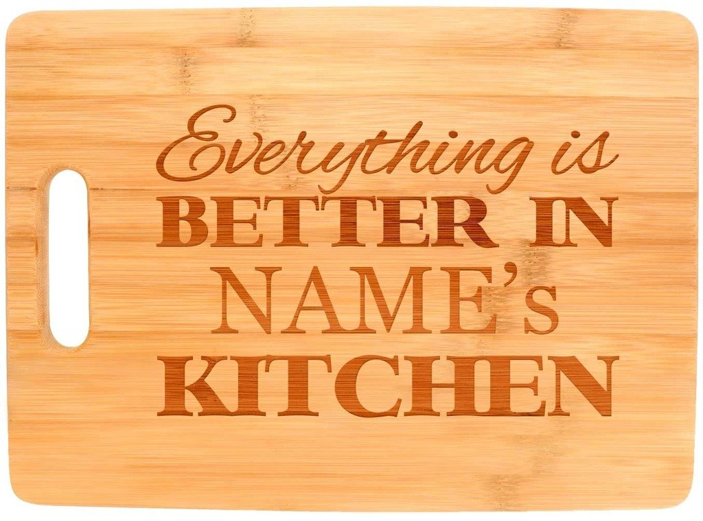 """A butting board with """"Everything is better in [Name's] Kitchen"""" etched on it."""