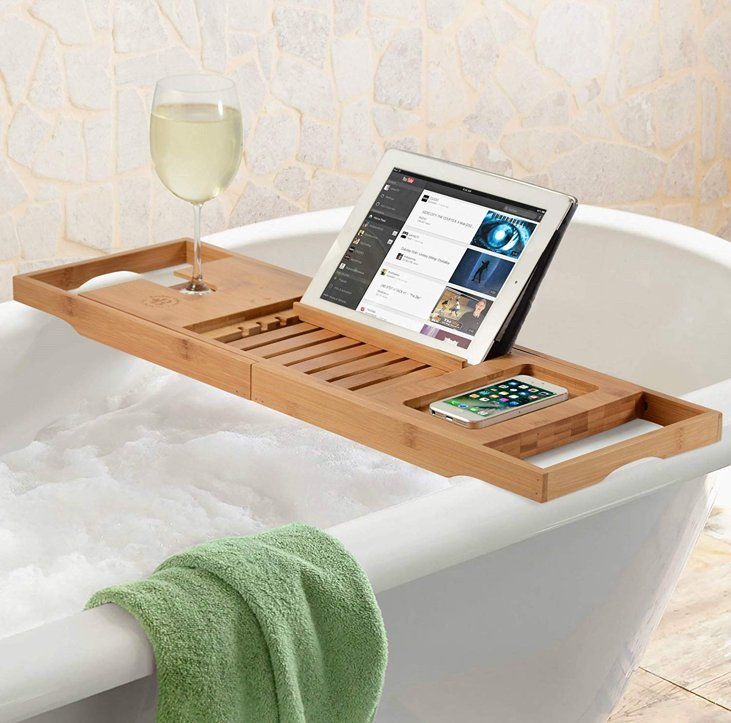 A bamboo bathtub tray over a tub holding an iPad and glass of wine.
