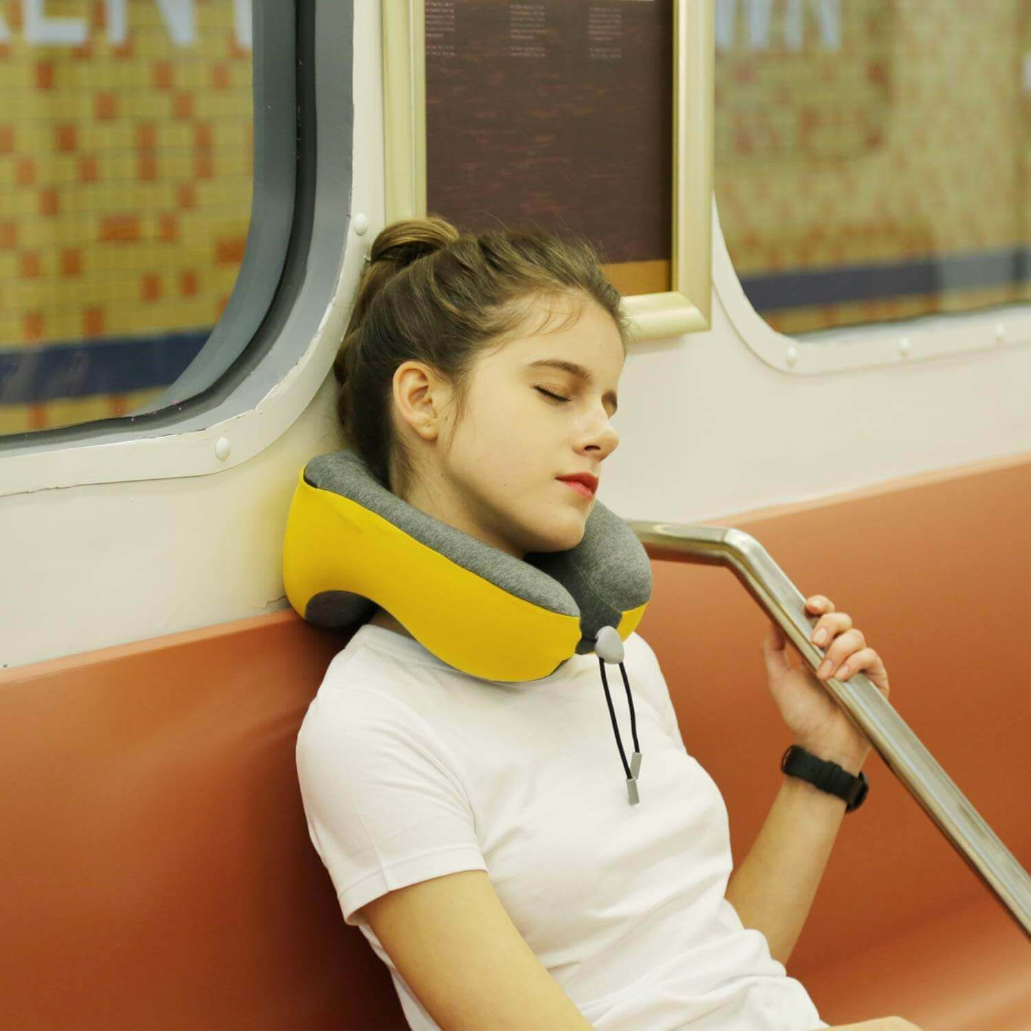 A person sleeping on a train with a neck pillow.