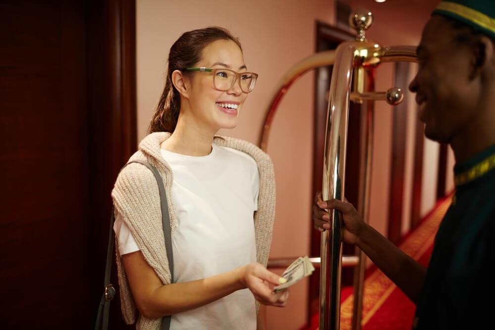 women tipping bellhop at hotel