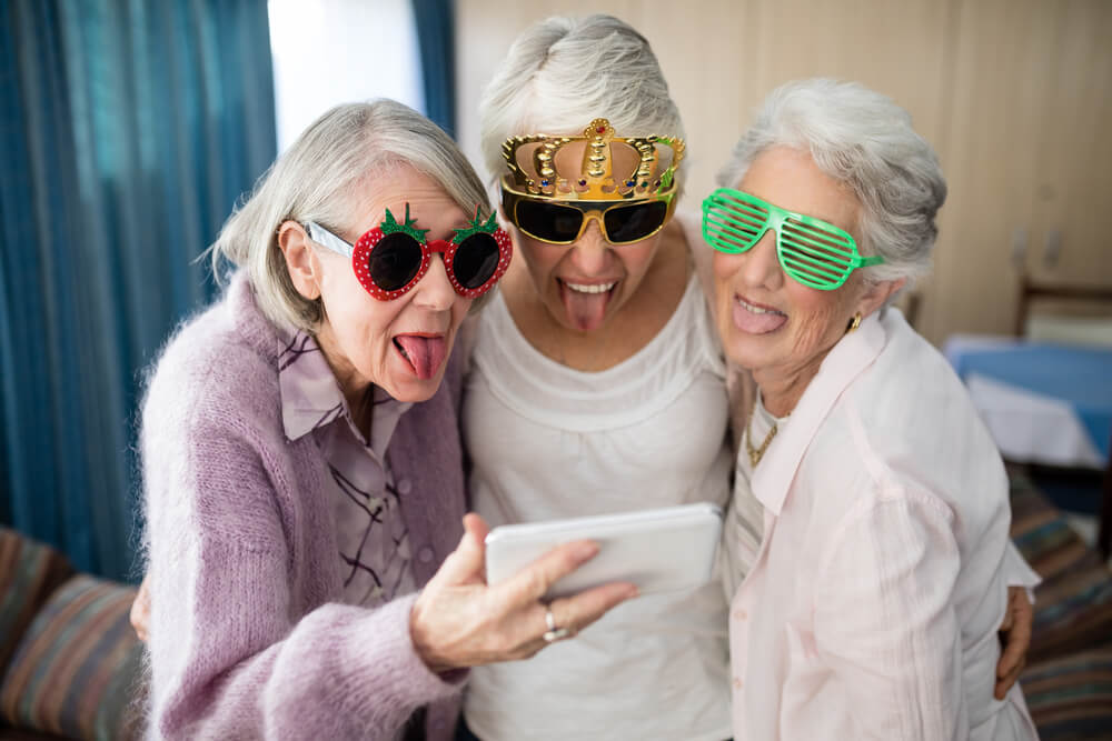 seniors in sunglasses sticking tongue out at camera