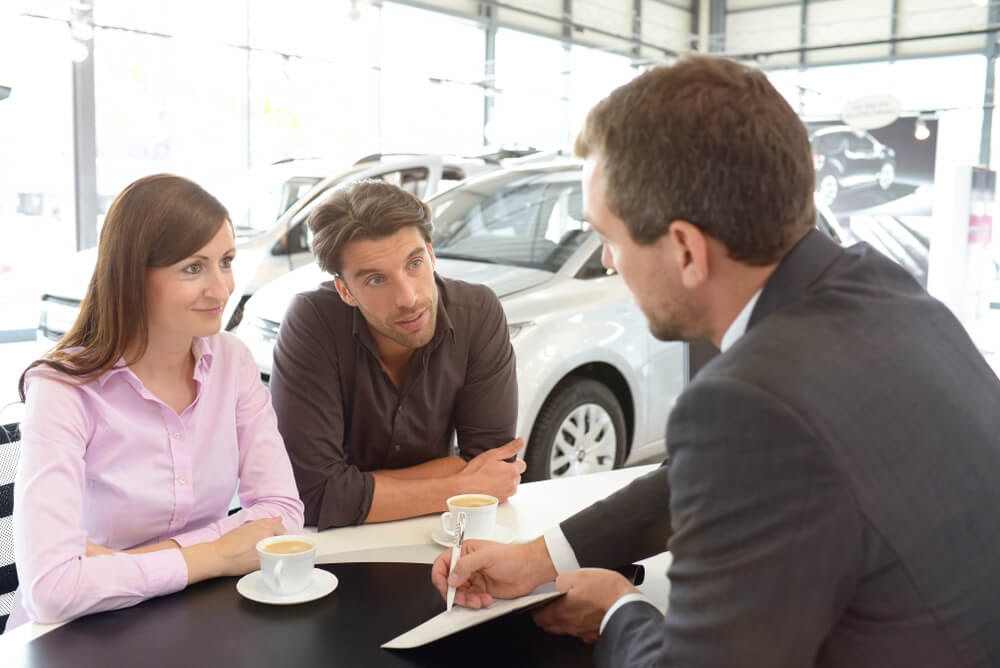 car salesman going over paperwork at dealer with couple