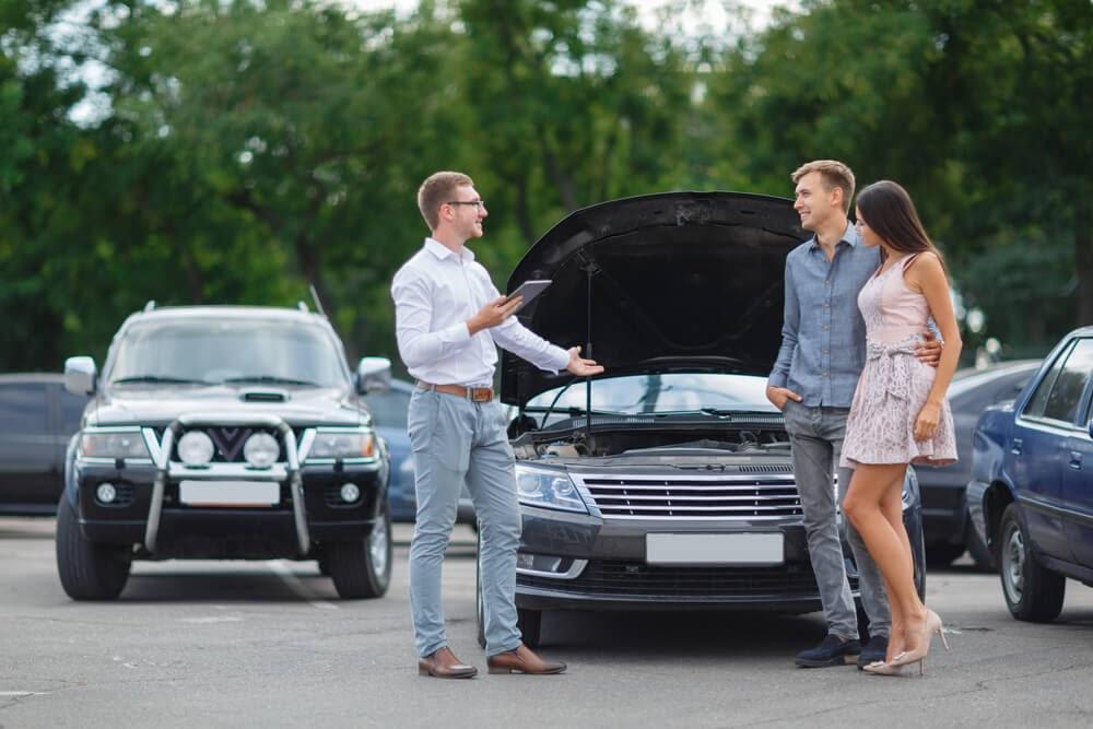 couple talking to car salesman