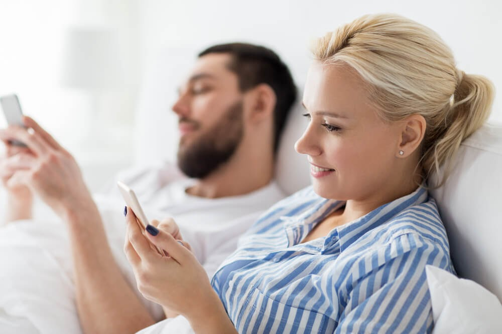 men and woman in bed on their phones