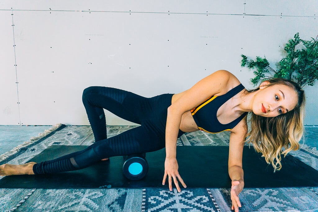 woman foam rolling outer thigh