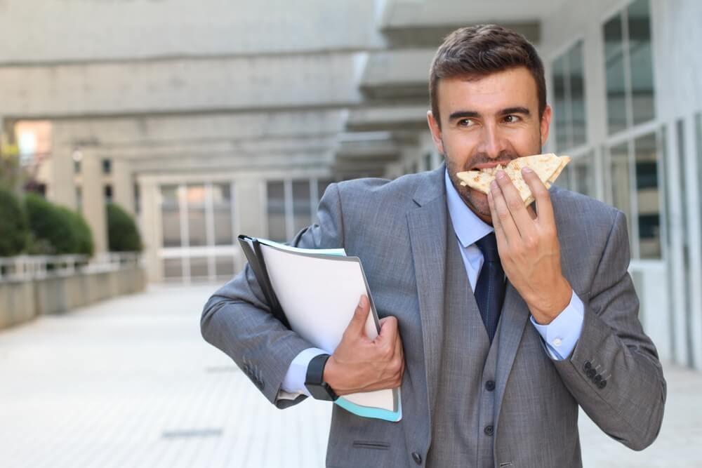 man eating breakfast sandwich on the go