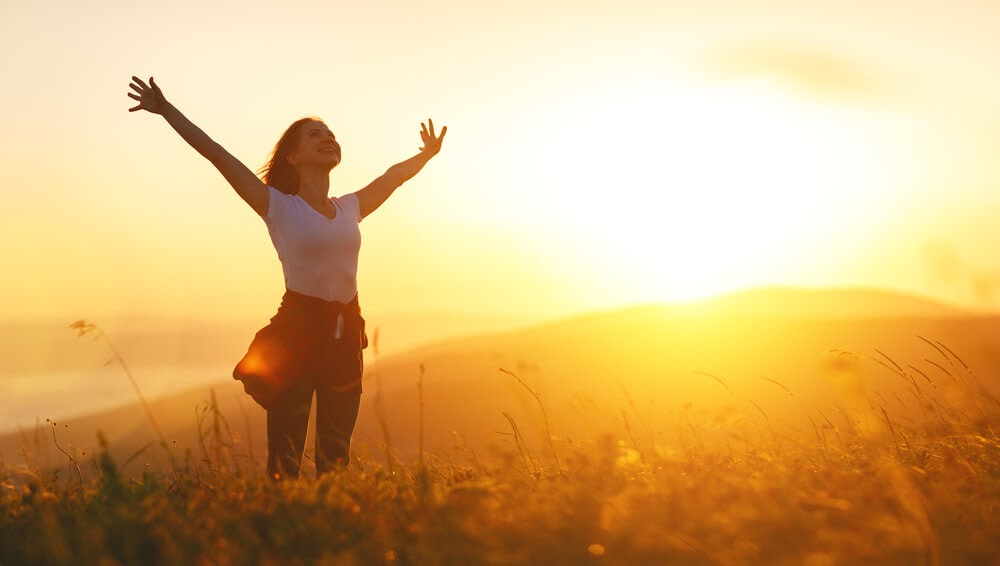 Smiling woman in a field with arms above head at sunset
