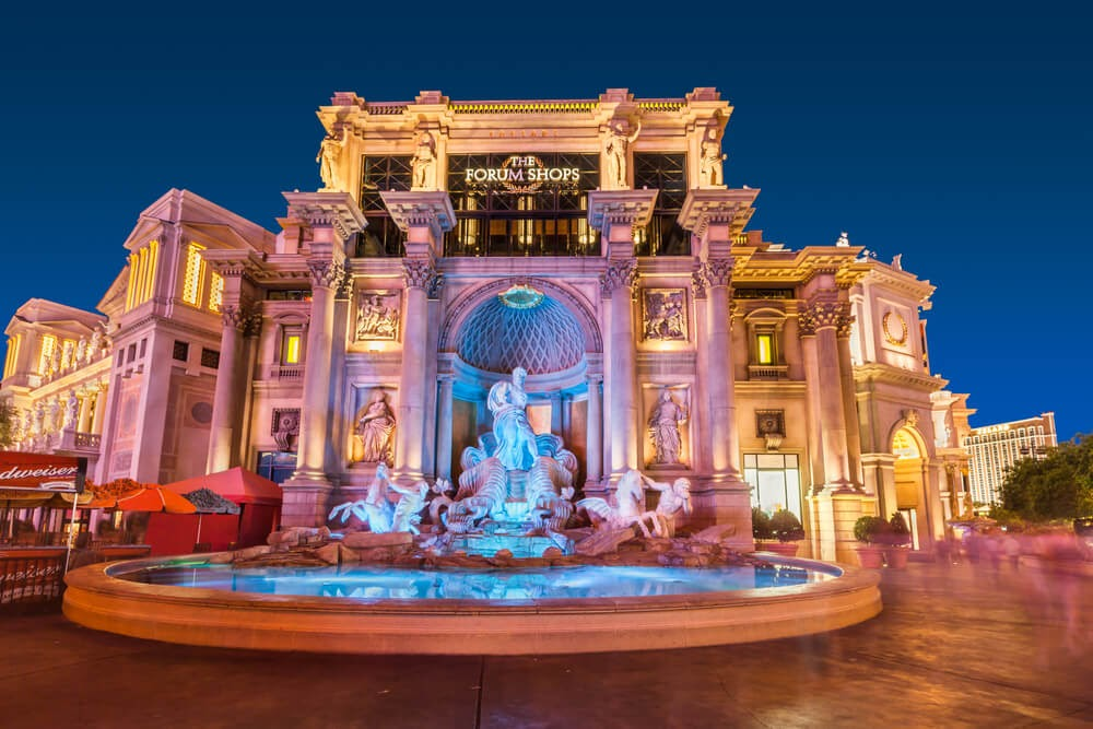 Large marble building with statues and glowing pond in front