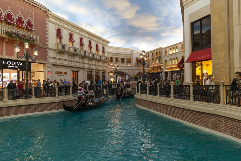 Gondolas float down canal and shoppers pass storefronts
