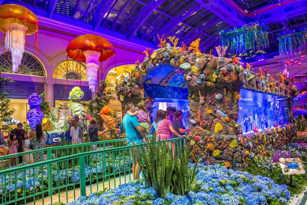Families walking through brightly colored indoor aquarium