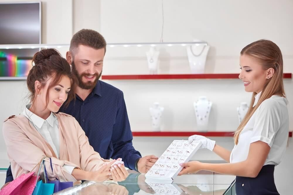 Couple looking at rings with saleswoman