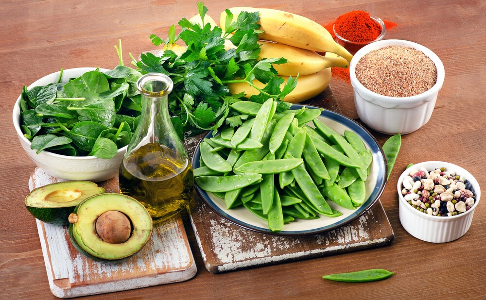 fruits, vegetables, beans, oil and spices on a board