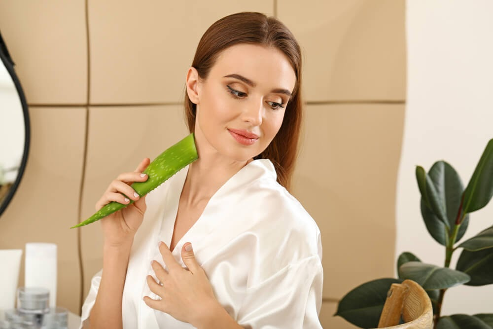 woman putting aloe vera plant on neck