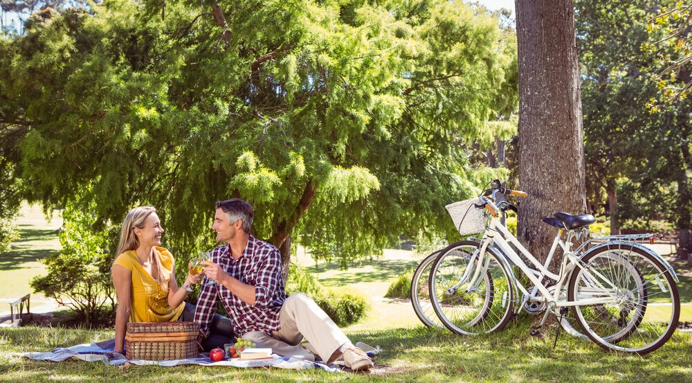 Couple sitting under a tree having a picnic