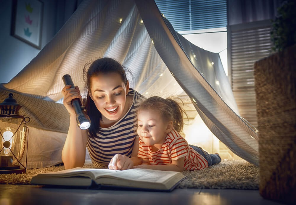 Woman and child in blanket fort reading by flashlight