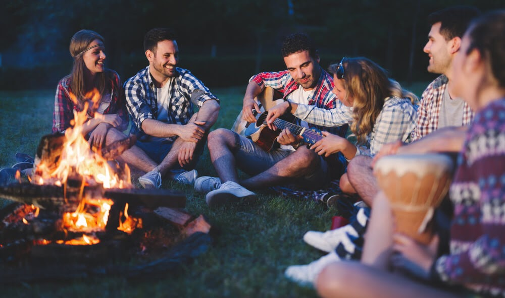 Group of people around a campfire with guitar and drum