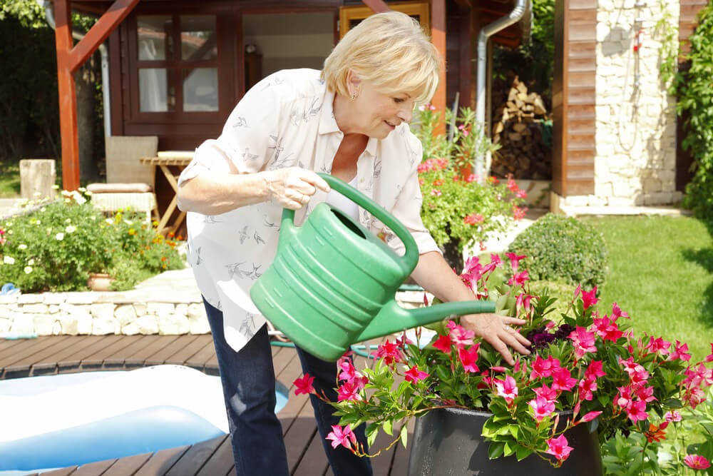 Older woman waters flowers with watering can.