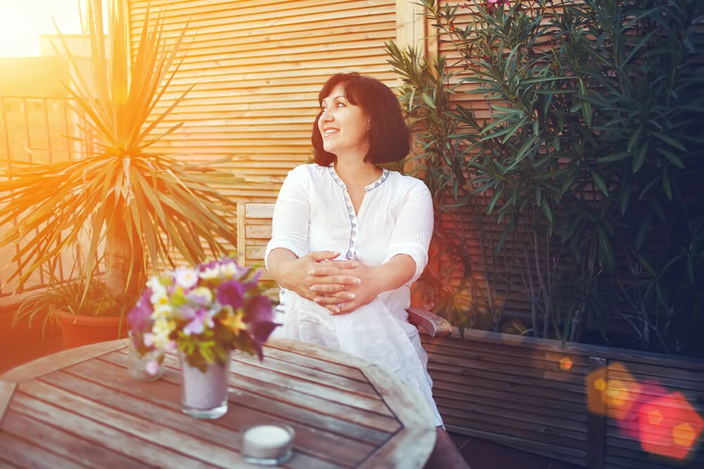 Woman sits on patio at golden hour surrounded by plants