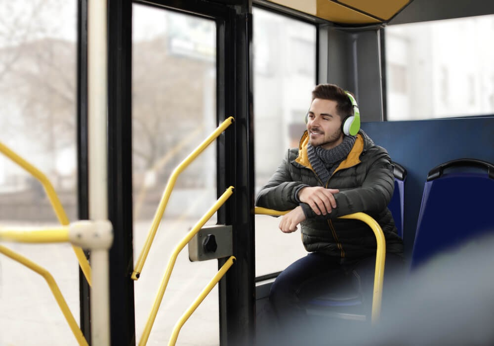 Man sitting on bus wearing headphones and smiling