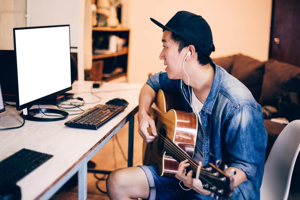 Young man playing guitar and looking at computer screen