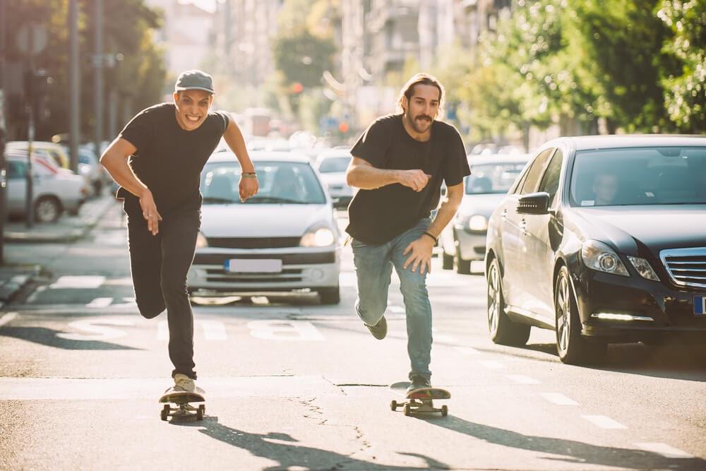 Two people skateboarding in traffic