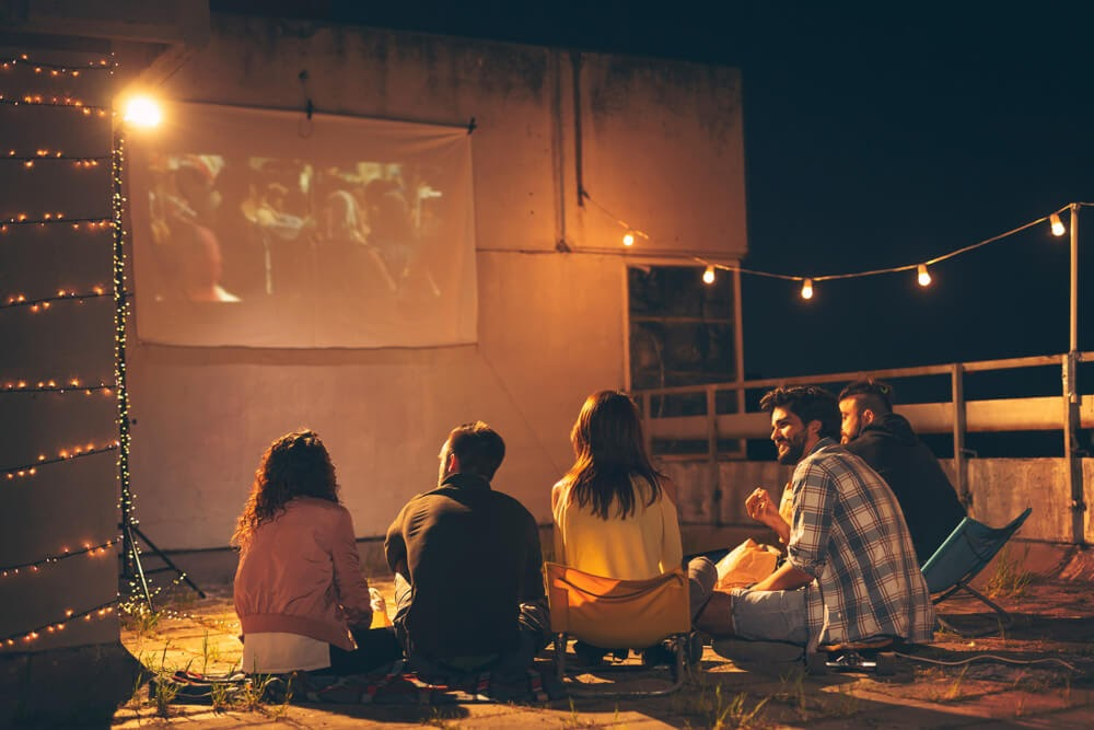 Group of people watching movie projected outdoors