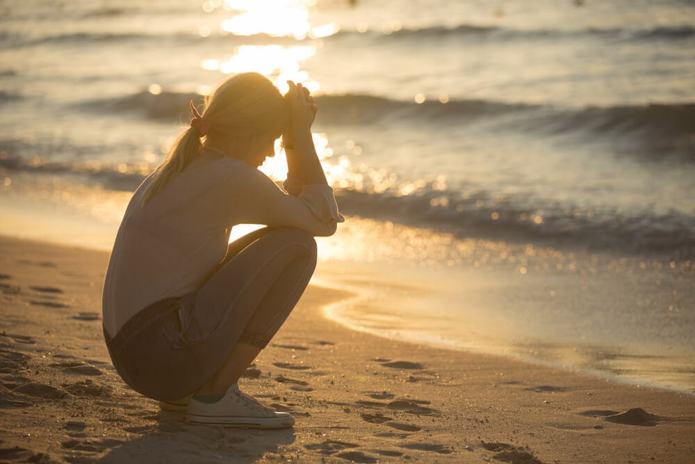 Woman kneeling on the beach with head in hands