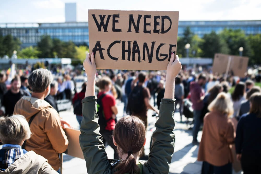 """Sign depicting the words, """"We Need A Change"""""""