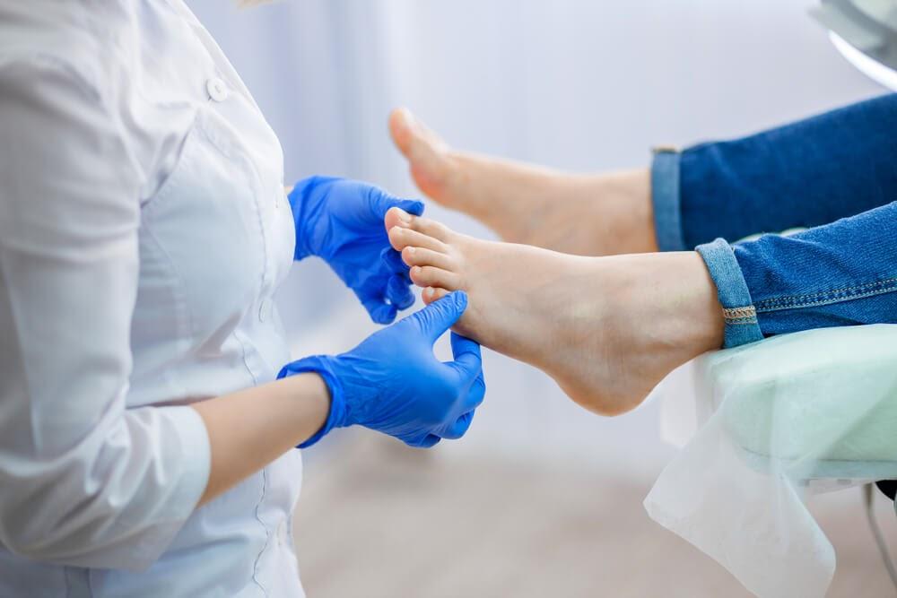 Gloved hands examine feet