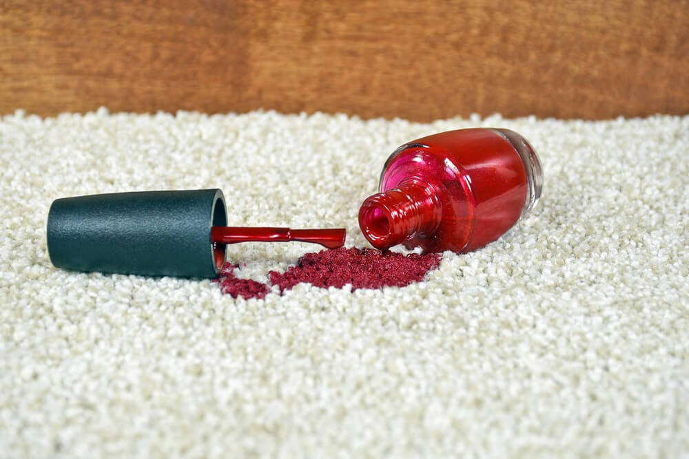 Red nail polish spilled on white rug