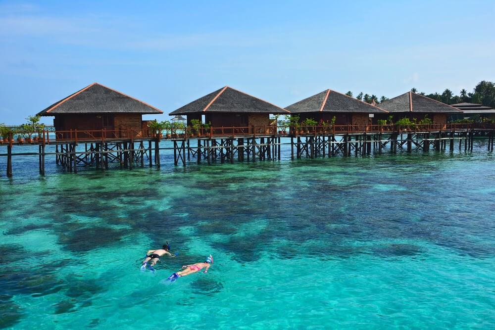Two snorkelers in blue water below huts on stilts in the water