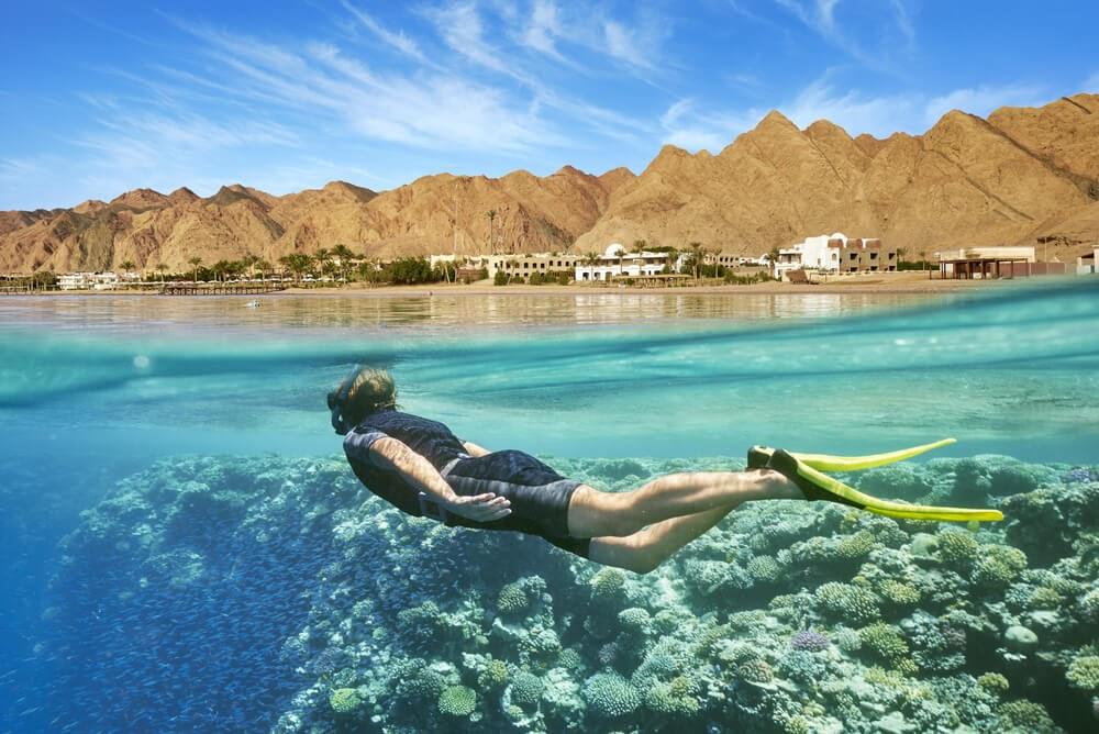 Half underwater angle of person snorkeling near the surface