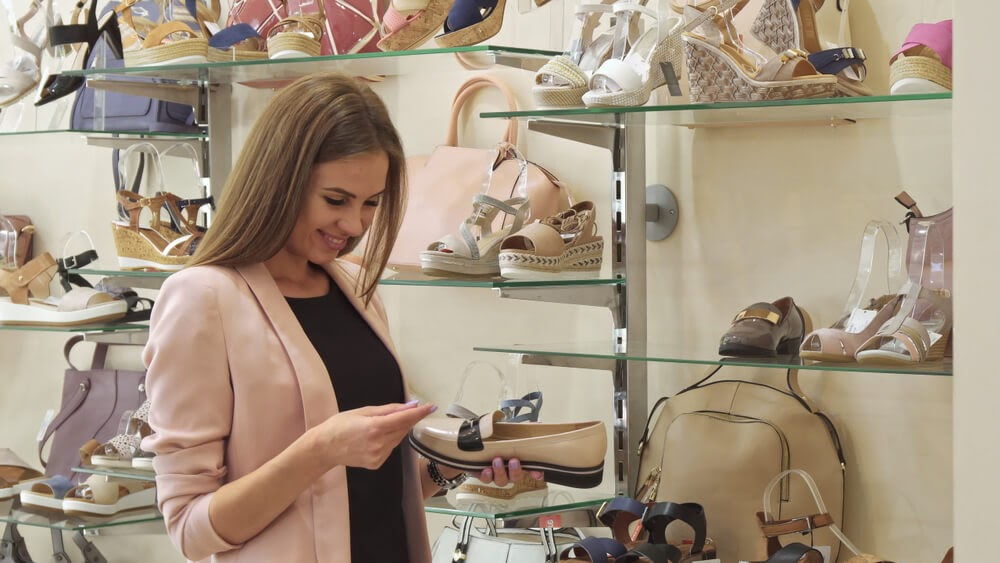 Woman in shoe store looks at price tag