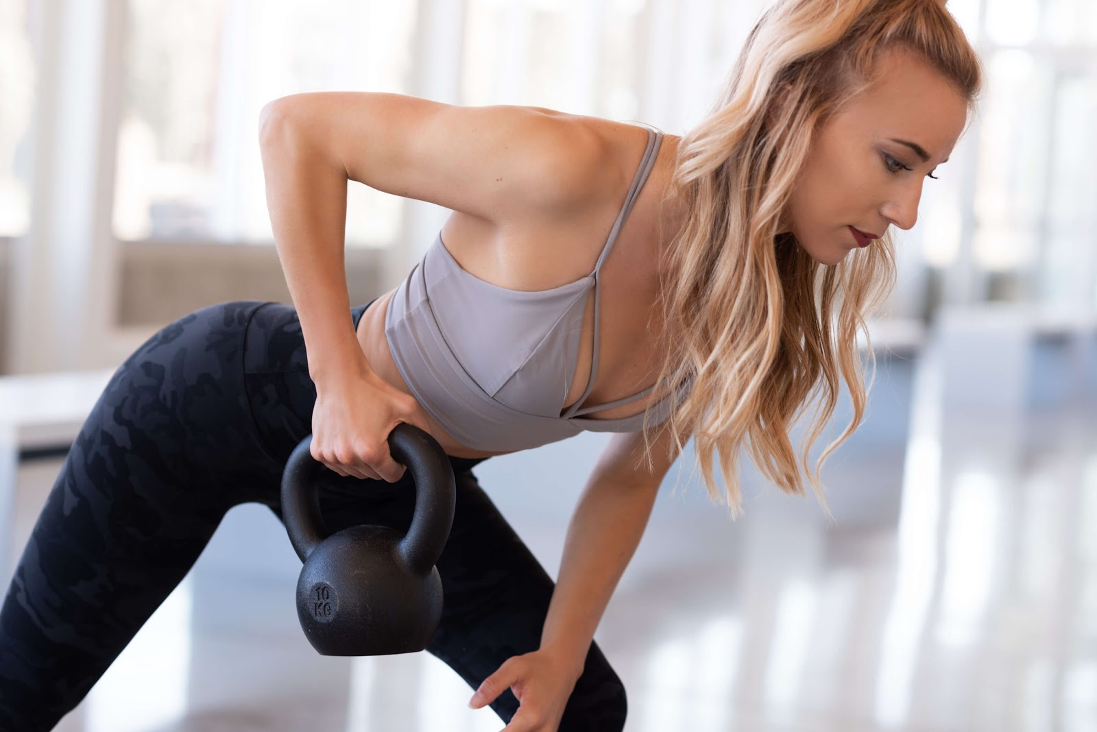 Woman performs a bent over row with kettlebell
