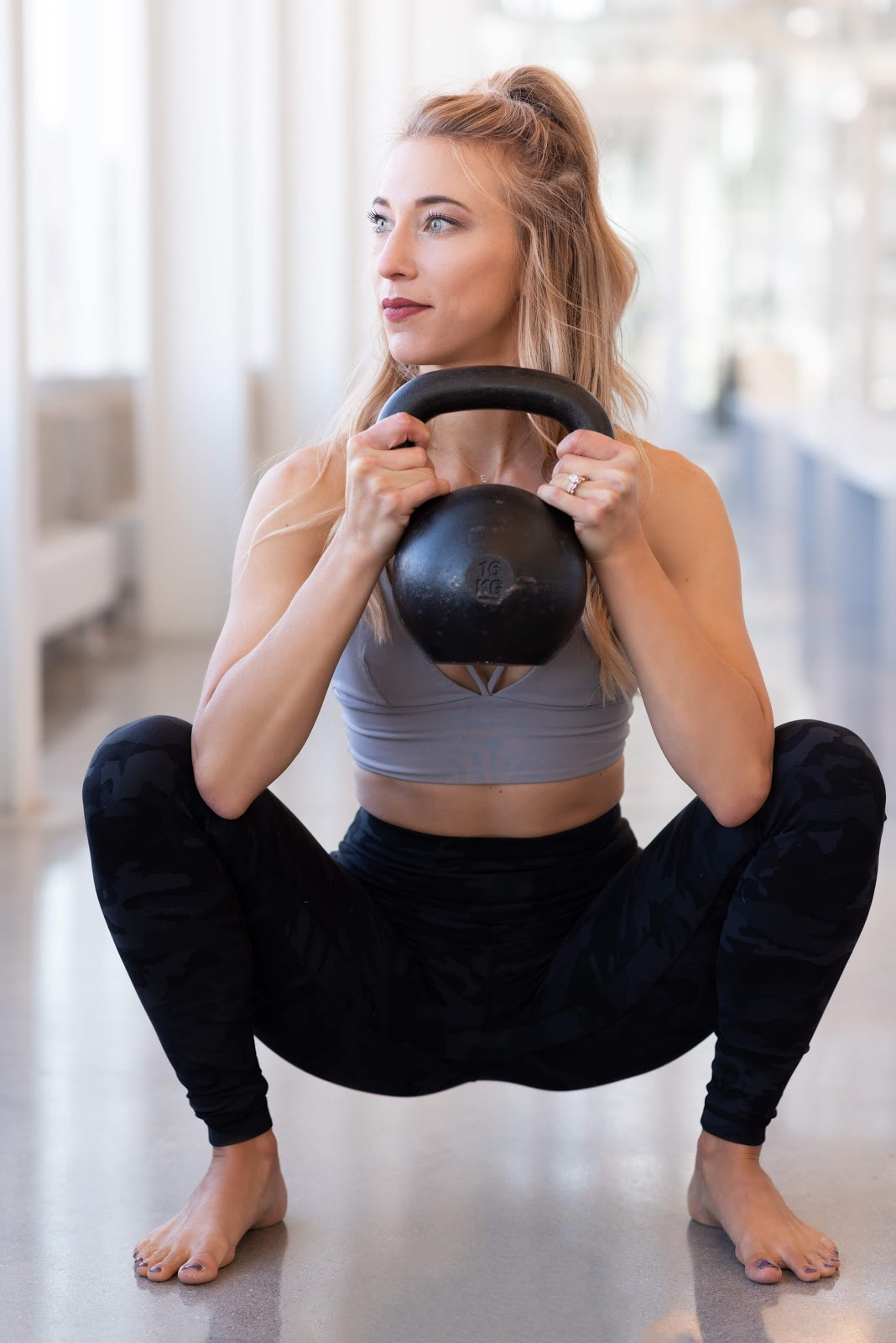 Woman performing goblet squat with a kettlebell