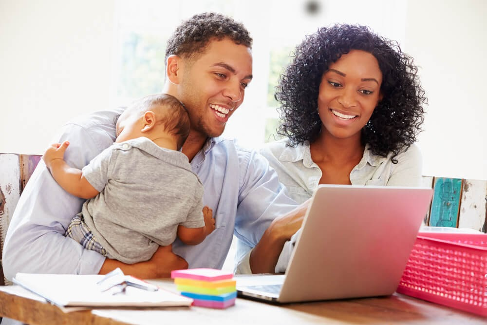 Couple with baby looking at laptop, smiling.
