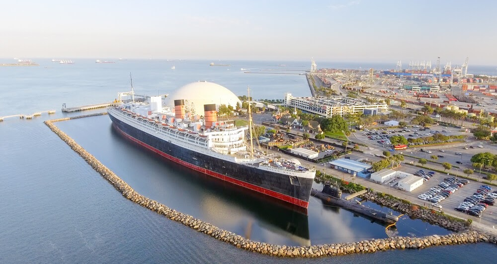 RMS Queen Mary. Large black and red boat docked in bay.